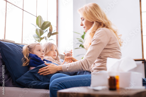 My poor girls. Loving worried fair-haired young mother giving a glass of cacao to kid and sitting near her children while her sick daughters lying in bed
