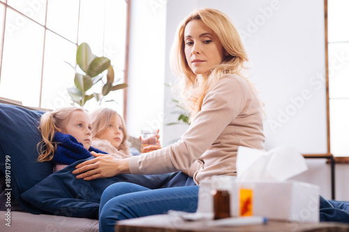 Feeling bad. Serious troubled fair-haired mother sitting near her children while her sick daughters lying in bed and looking at the medications lying on the table