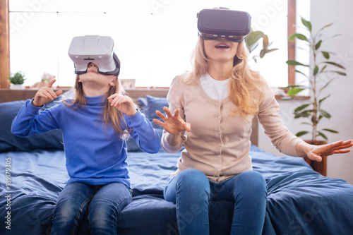 Virtual reality. Concentrated excited blond mother and daughter wearing VR headset and playing while sitting on the bed