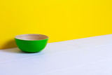 Bamboo green plate on white wooden table, yellow color paper background, paper pattern, side view, copyspace