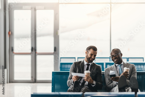 happy business colleagues waiting for flight in airport lobby