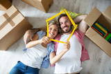 Attractive young couple relax between boxes on floor at new apartment - 189207766