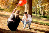 Happy young parents with baby boy in autumn park holding red balloons - 189210105
