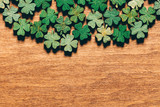 Wooden green shamrocks laying on the wooden floor. - 189211316