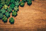 Green wooden four leaf shamrocks on wooden board - 189211363