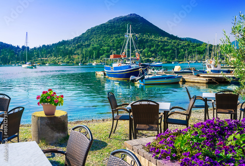 Beautiful view over terrace near the beach with flowers on table in Nydri villaga, seaport of Lefkada, in Greece