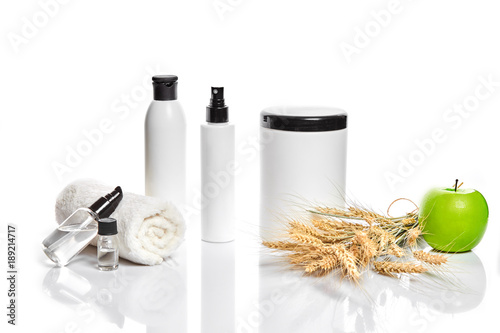 Papiers peints Spa Spa cosmetics, jar of cream, oil with wheat, white cosmetic bottles with apple and wheat towel, candle, soap isolated on white. Without label.