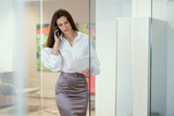 young and beautiful businesswoman talking on the phone in a glass office and keeps documents - 189224113