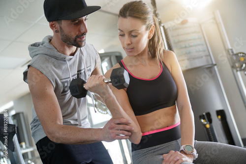 Fitness girl working out with personal trainer in gym