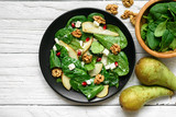 vitamin salad with spinach leaves, pear, nuts, pomegranate and feta cheese in black plate - 189230368