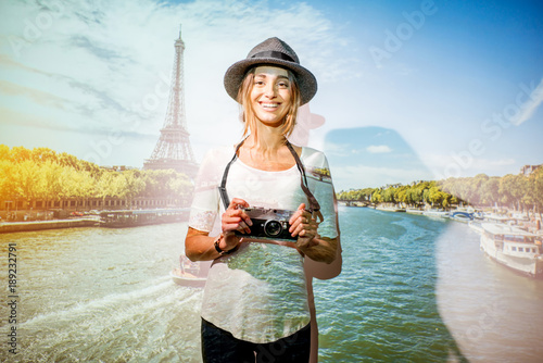 Foto Murales Portrait of a young woman traveler with projected image of landscape view on Paris with Eiffel tower