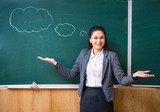 indecisive teacher standing at the blackboard - 189234516