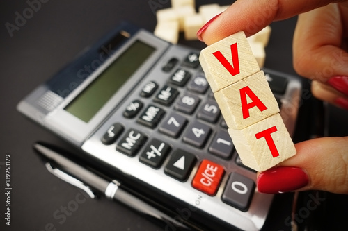 VAT calculation concept with woman hand holding vat word on wooden cubes above calculator keyboard on dark background