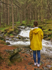 Woman in a yellow raincoat infront of a creek in the Dolomites