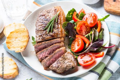 Foto op Aluminium Steakhouse Grilled beef striploin steak with fresh salad.