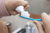 hands with toothpaste and toothbrush