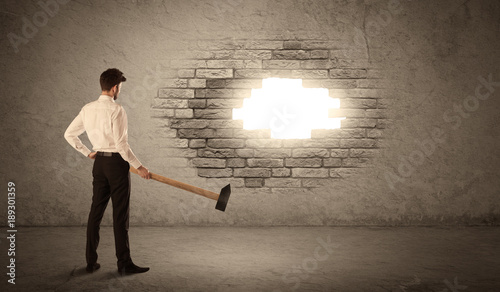 Fotobehang Graffiti Business man hitting brick wall with hammer and opening a hole