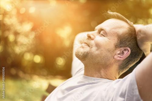 Leinwanddruck Bild Mann entspannt in der Sonne - genießt Freizeit - macht Power Napping