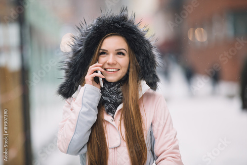 Young woman using smart phone mobile device at winter snowy day