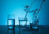 Creative splashing water in the glass on blue background. - 189316905