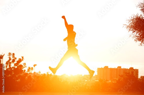 Man running and jumping with sunset in background