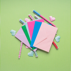 Colorful pastel pens, envelopes and hearts on green. Valentine mother day