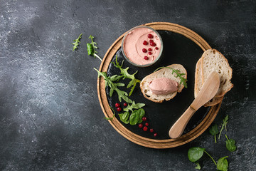 Chicken homemade liver paste or pate with sliced whole grain bread, knife, cranberries, green salad served in glass jar on wooden slate serving board over black texture background. Top view, space
