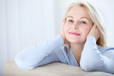 Active beautiful middle-aged woman smiling friendly and looking in camera. Woman's face closeup. Realistic images without retouching with their own imperfections. Selective focus. - 189325379
