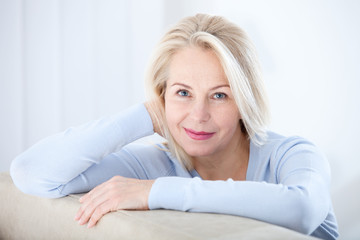 Active beautiful middle-aged woman smiling friendly and looking in camera. Woman's face closeup. Realistic images without retouching with their own imperfections. Selective focus. © missty