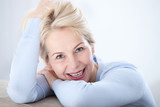 Active beautiful middle-aged woman smiling friendly and looking in camera. Woman's face closeup. Realistic images without retouching with their own imperfections. Selective focus. - 189325500