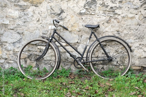 Fotobehang Fiets Old bike standing on grass in front of old stone wall
