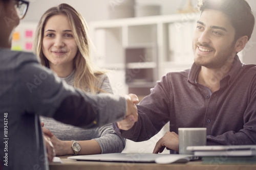 Young couple shaking hands with a female agent