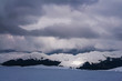 Beautiful view of the winter ski resort. Mountains with clouds, in the distance ski lift.