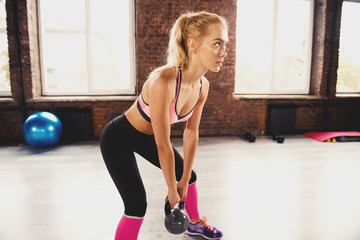Blonde girl working out at the gym with a kettlebell. crossfit exercise