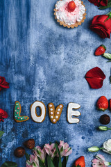 top view of flowers and Love cookies on shabby background for valentines day