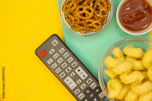 Weekend, Leisure, Lifestyle Concept A remote control, salty pretzels, corn chips and ketchup on a bright one-colore yellow background Poster