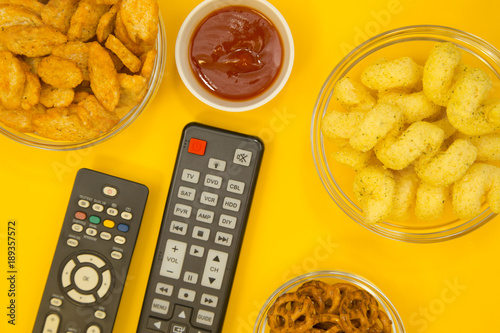 Weekend, Leisure, Lifestyle Concept Two remote controls, salty pretzels, bread crumbs, corn chips and ketchup on a bright one-colore yellow background Poster