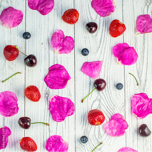 Fotobehang Kersen Rose petals, strawberry, blueberry and cherry on light wooden background.