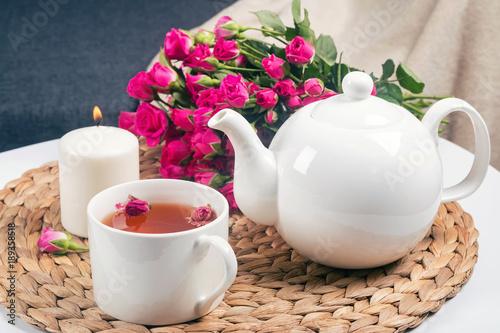 krautertee-kerze-teekanne-und-schone-rosen-auf-dem-tisch