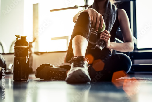 Sport woman sitting and resting after workout or exercise in fitness gym with protein shake or drinking water on floor. Relax concept. Strength training and Body build up theme. Warm and cool tone - 189360999