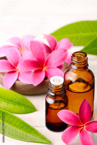 Plexiglas Plumeria Frangipani Absolute Oil and red plumeria flowers on the wooden table