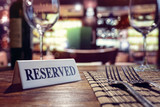 Reserved sign on restaurant table with bar background