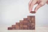 Close up Woman hand arranging wood block stacking as step stair. Business concept growth success process. - 189379119