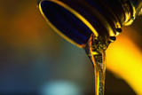 Liquid stream of clean oil flows from the neck of the plastic bottle close-up. - 189384712