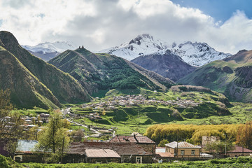 Beautiful view of the Georgian village and Mount Kazbek, at the foot of which is Gergeti Trinity Church.