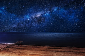 Night starry sky over the beach with a pier.