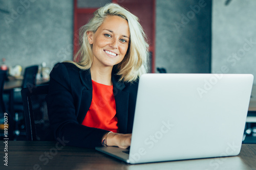 Smiling young businesswoman working at laptop