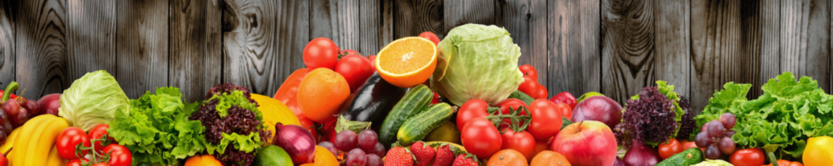Fruits and vegetables on background of wooden wall. Healthy vegetarian food.
