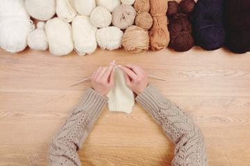 Dressmaker workplace. Woman female girl hands knitting warm clothes by knitted needles on wooden background with line of balls of thread