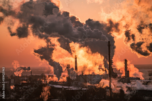Foto op Plexiglas Oranje eclat the chimneys of a refinery with smoke and steam with the pinkk sunset on the background